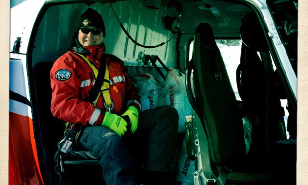 Robb Andersen sits with the explosives in the back seat just before starting a heli-bombing mission.