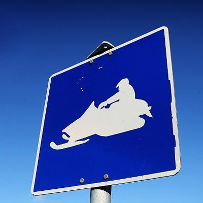 Blue sign with snowmobile graphic.