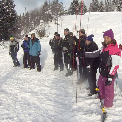Group of people participating in Avalanche Awareness seminar, outside in snowy field.