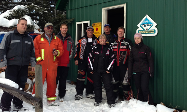 A group of riders in snowmobile gear stand outside a green corrugated cabin in the snow.