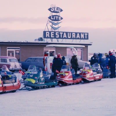 A picture of a line-up of snowmobiles parked outside a diner on a winter day.