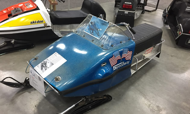 Speedway snowmobile, painted metallic blue in colour, with crossed American flags logo and 'Speedway' painted on side.
