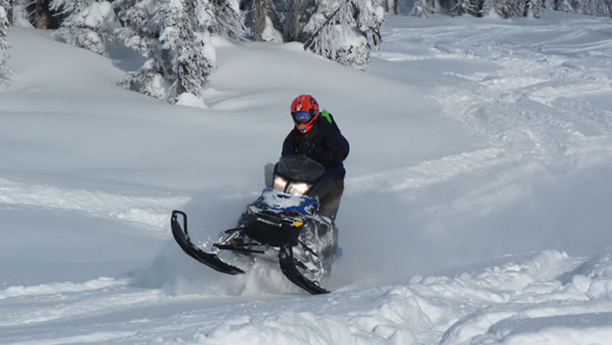 A snowmobiler carves up some deep powder in Blue River.
