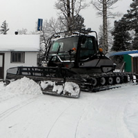 A snowmobile trail groomer is sitting in front of the Pepper Hill Cabin near Edson, Alberta.