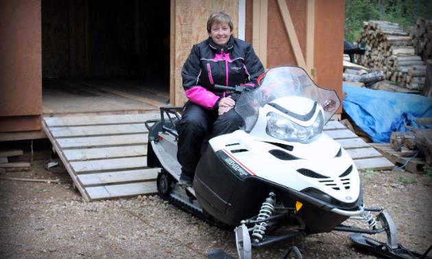 Brenda Duval waits for snowfall on her Polaris Shift snowmobile.