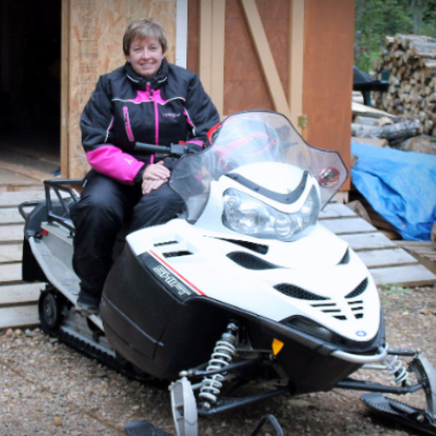 Brenda Duval waits for snowfall on her Polaris Shift snowmobile.