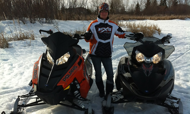 Woman in snowmobile suit stands between two snowmobiles