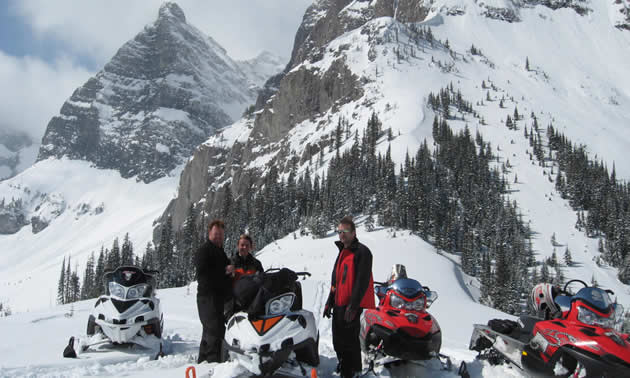 Two men, a woman and four snowmobiles stand on snowy ground before a stark mountain range