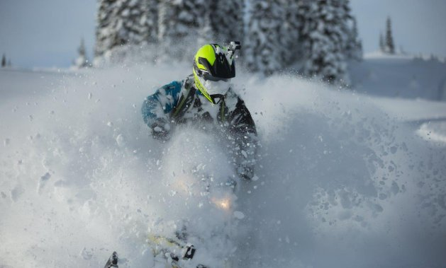 A sledder with a face and sled full of snow.