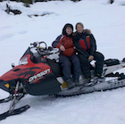 Two women sitting on top of parked snowmobile.