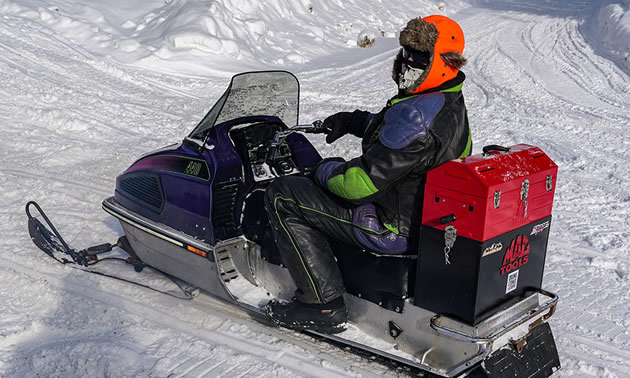 Kris Peltzer is shown here riding an old Arctic Cat 440 complete with custom Mac Tools tool box strapped on the back of his machine.
