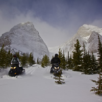 Three snowmobilers in a dramatic mountain landscape
