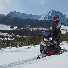 Jennifer Dewar-Jones on her sled overlooking a valley in the Crowsnest Pass.