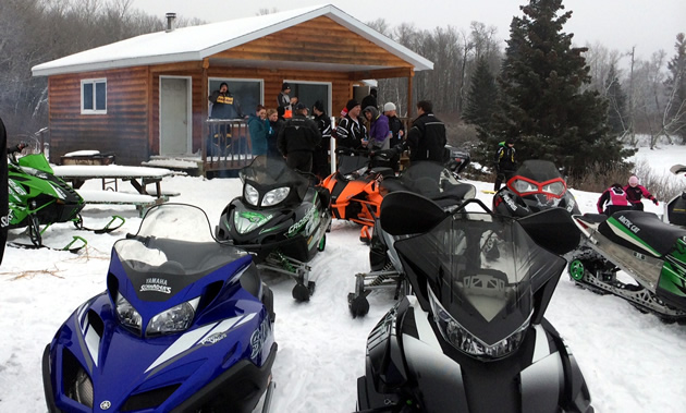 A group of sledders are gathered around Green Lake Shelter in Duck Mountain Provincial Park, Saskatchewan.