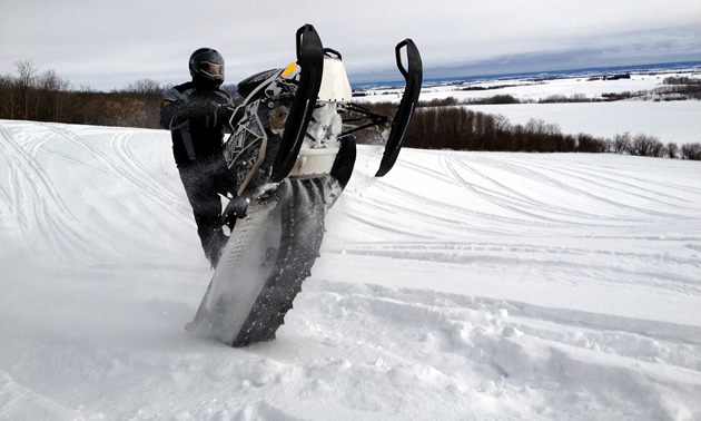 A snowmobiler cat walks his sled in the open fields around Kamsack, Saskatchewan.