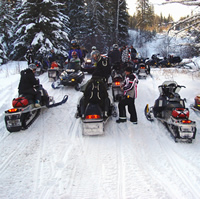 Snowmobilers stop for a break on the trail to Pepper Hill Cabin near Edson, Alberta, on the way to Silver Summit ski area.