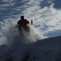 Erik catching some air on the Saskatoon Snowmobile Club's trails, while wearing a chest protector for safety.