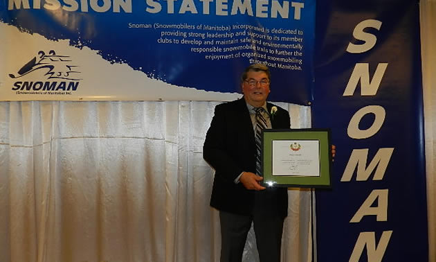 Man in dress suit standing on a stage holding a framed certificate.