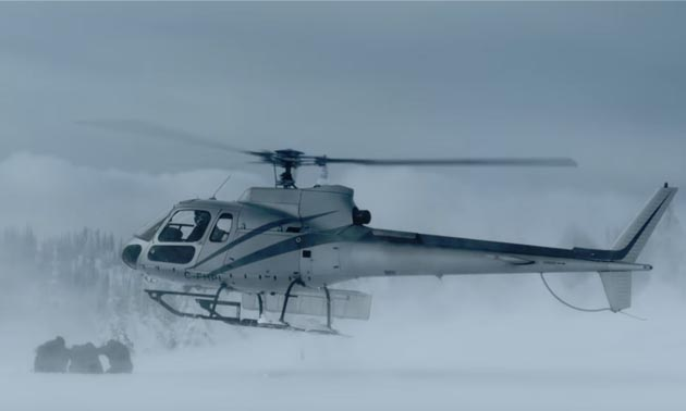 Still of sledders and helicopter in blizzard.