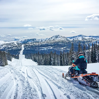 Snowmobiler riding on snowy trail.