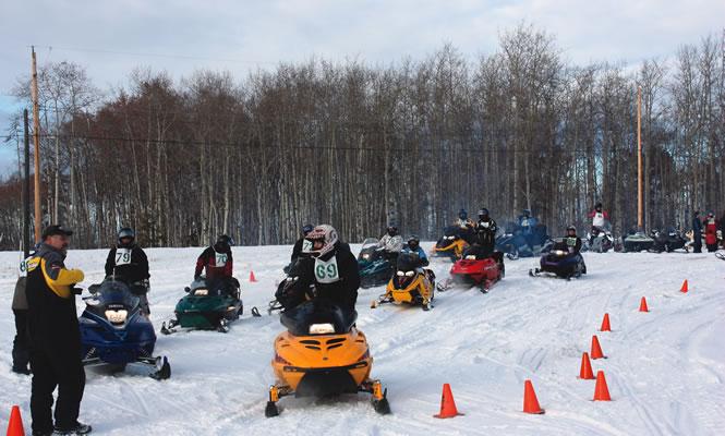 snowmobilers manoeuvring around orange cones