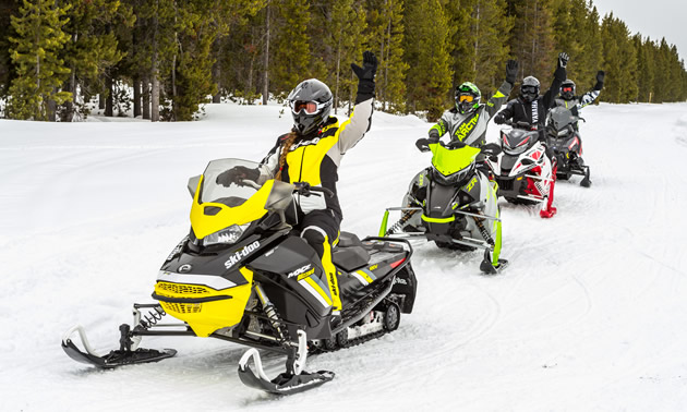 Group of snowmobilers out on a trail.