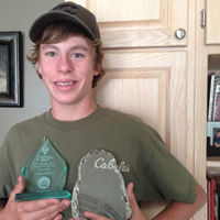 Teenage boy wearing a baseball cap and T-shirt holds two plexiglass awards