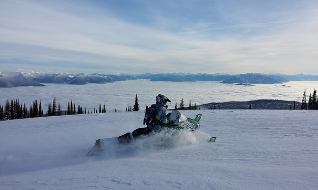 Heather White on her sled overlooking a vista of mountains peaking through the cloud cover.