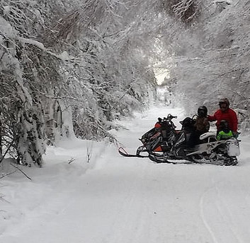 Two sledders stopped on a snow-covered trail near Whitecourt, Alberta.