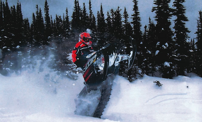 a snowmobiler riding vertical