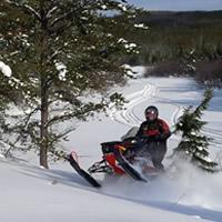 Marcel Dalpe shreds his Ski-Doo through a clearing near Hudson Bay, Saskatchewan.
