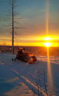 A snowmobile and a beautiful sunset in Hudson Bay, Saskatchewan.
