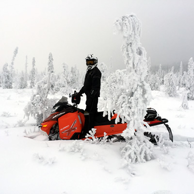 A snowmobiler standing on his ride next to a snowy tree in Wildcat Hill Provincial Park near Hudson Bay, Saskatchewan.