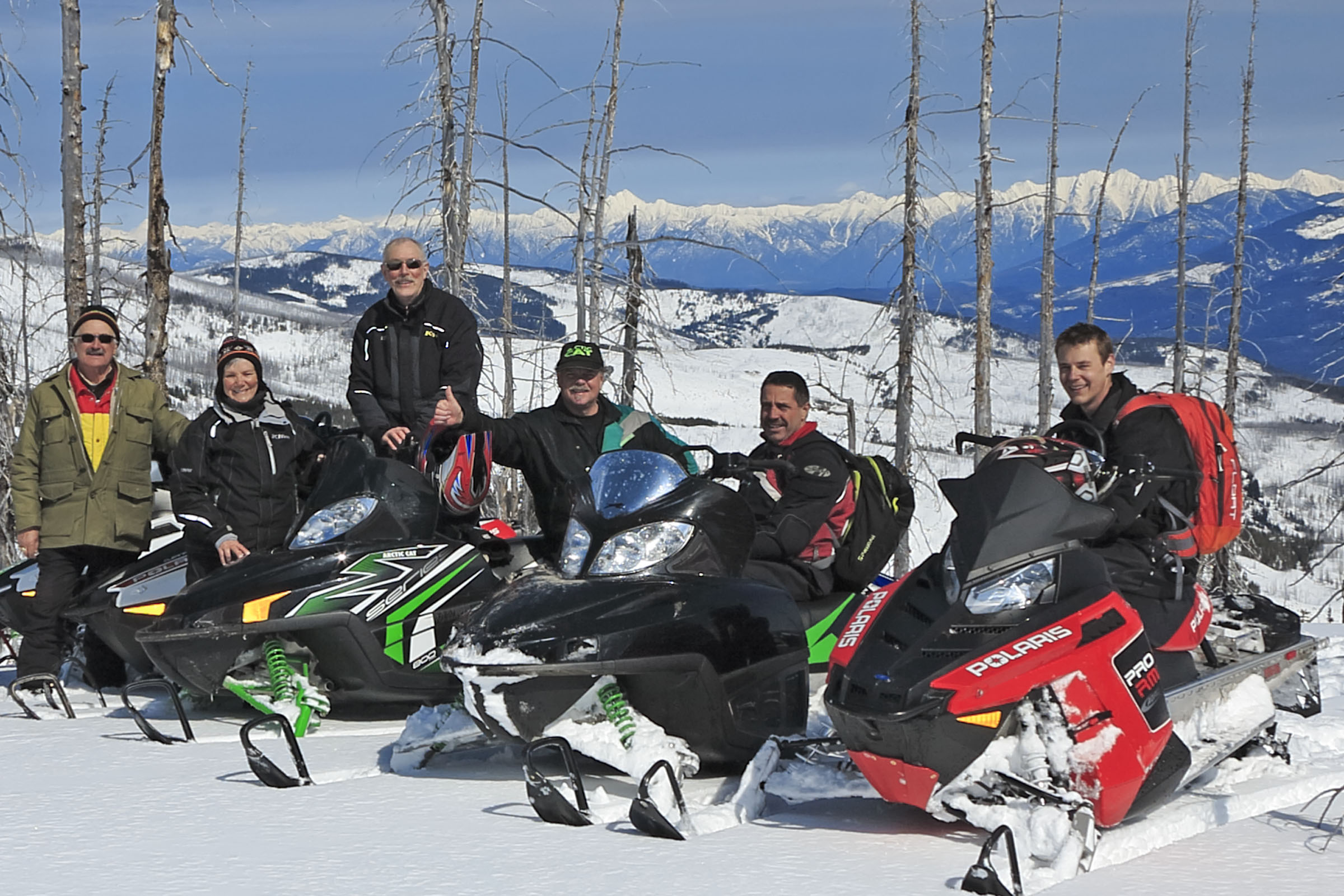 A group of sledders with the Steeples mountain range and Fisher Peak behind them.