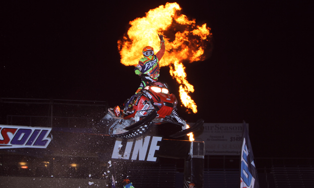 A snocross racer taking a jump and punching the sky with a fire ball behind him.