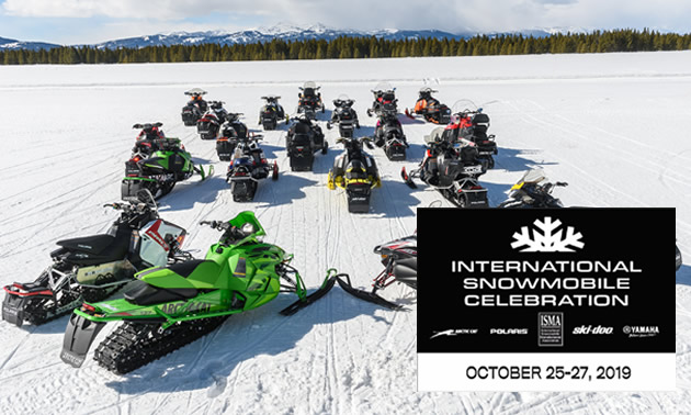 Group of sledders in a circle, with logo of the International Snowmobile Manufacturer's Association logo.