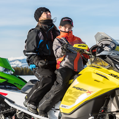 Two people out enjoying a snowmobile ride.