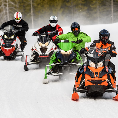 Group of snowmobilers on trail.