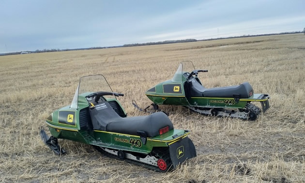 Two John Deere Cyclone sleds sitting out in a field.