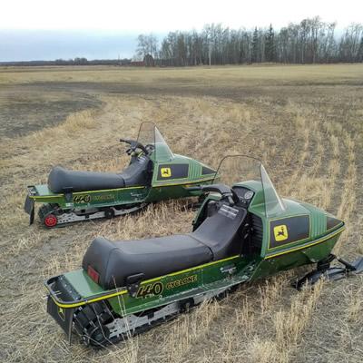 Two John Deere Cyclone sleds in a farmer's field.