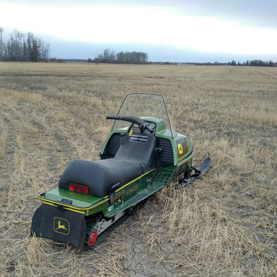 One John Deere Cyclone sled sitting out in a farmer's field.