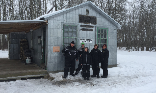 Members pose in front of the Sno-Drifters' Hide Out warm-up shelter. This shelter is located just south of Kamsack before Rhein.