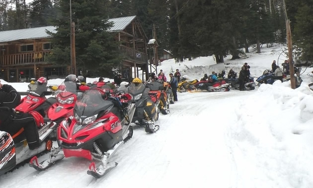 Line up of snowmobiles and people getting geared up.