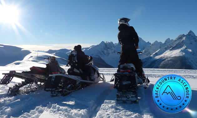 Panorama picture of sled in foreground with blue skies and mountains in background.
