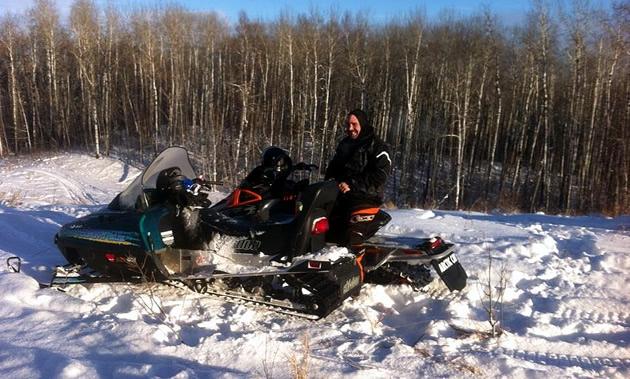 Sledders pause during a bluebird day in Alberta's Lakeland region.