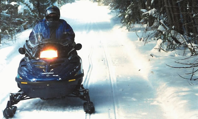 person riding a snowmobile on a trail