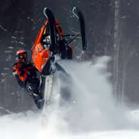 Kristien Larouche jumps his Polaris sled on a mountain slope.