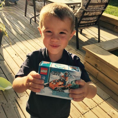 Picture of Grayson holding up package of LEGO.