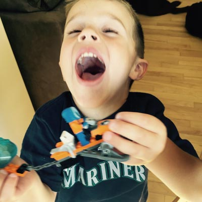 Grayson laughing and holding his LEGO.