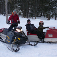 Family on vintage snowmobile